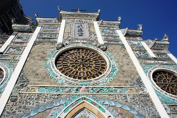 牌楼上嵌有各种中式山水花鸟泥雕彩塑,开了三个西洋玫瑰彩窗