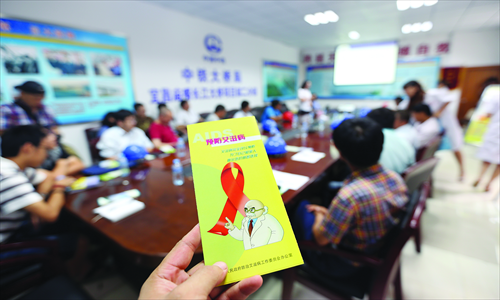 Workers from the Yichang Center for Disease Control and Prevention in Hubei Province pass on knowledge about AIDS prevention and control to migrant workers on August 31. Photo: CFP